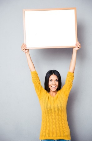 Portrait of a smiling woman holding blank board over gray background