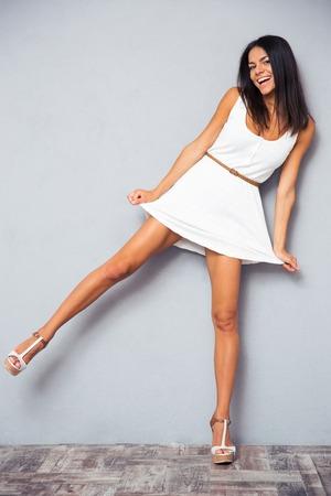 In voller Länge Portrait eines lustigen glückliche Frau, die auf einem Bein über grauem Hintergrund und auf Kamera