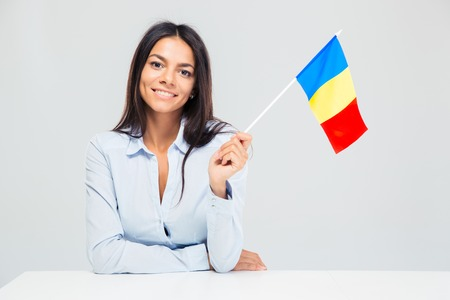 Smiling young woman sitting at the table with romanian flag isolated on a white background. Looking at camera