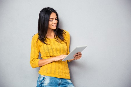 Smiling young woman using tablet computer over gray background