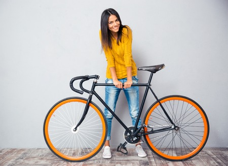 cyclist: Full length portrait of a smiling woman standing near bicycle on gray background. Looking at camera