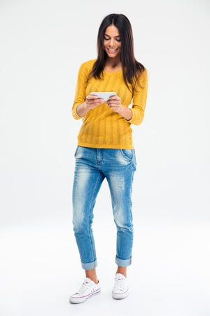 cuerpo entero: Retrato de cuerpo entero de una joven feliz que usa smartphone aislado en un fondo blanco