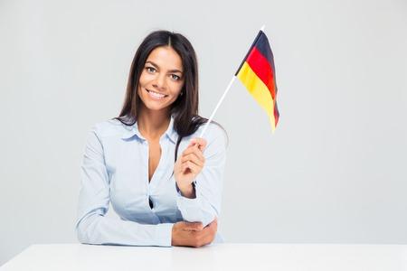 bandera alemania: Empresaria joven sonriente sentado en la mesa y sosteniendo el indicador de Alemania aislado en un fondo blanco