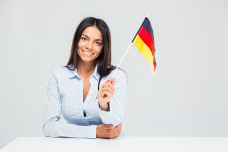 Smiling young businesswoman sitting at the table and holding germany flag isolated on a white background