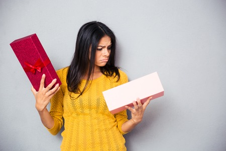 confusion: Unhappy young woman holding gift box over gray background
