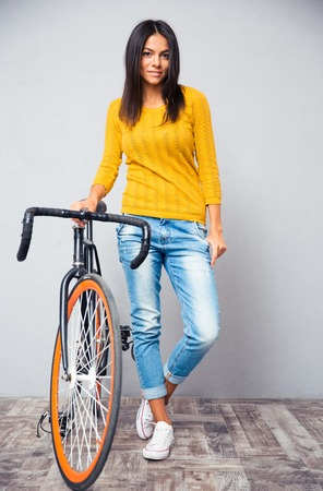 cycler: Full length portrait of a happy woman stnading with bicycle on gray background and looking at camera