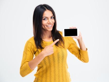 쾌활 한 귀여운 여자 흰색 배경에 고립 된 스마트 폰 화면에 손가락을 가리 킵니다. 카메라를 보면서
