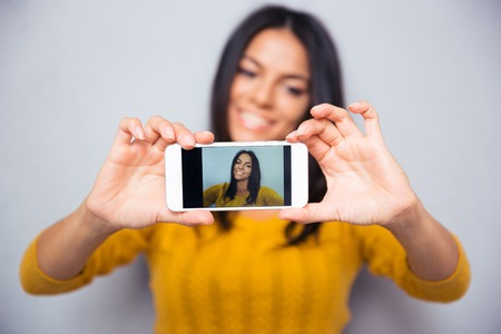 attitude girls: Happy woman making selfie photo on smartphone over gray background. Focus on smartphone