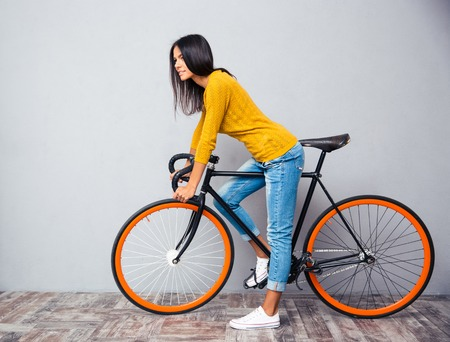 cycler: Full length portrait of a charming woman with bicycle on gray background. Looking at camera Stock Photo