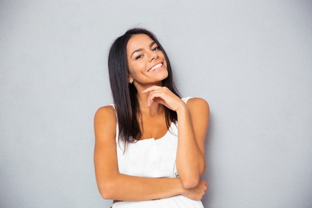gorgeous: Cheerful young woman looking at camera over gray background