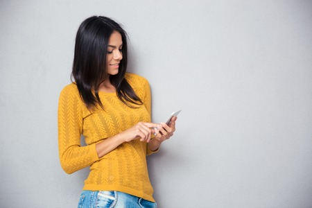 Happy casual woman using smartphone over gray background
