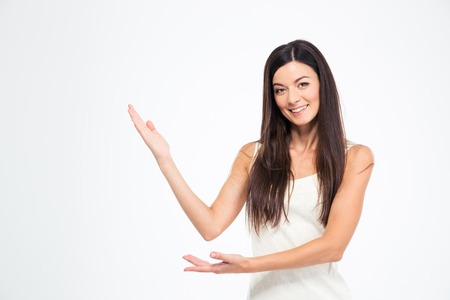 Happy young woman showing welcome gesture with hands isolated on a white background. Looking at camera