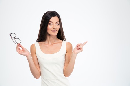 19's: Hapyp woman holding glasses and pointing finger away isolated on a white background