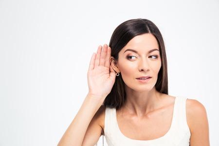 oreja: Mujer hermosa que pone la mano en la oreja para oír mejor aislado en un fondo blanco Foto de archivo