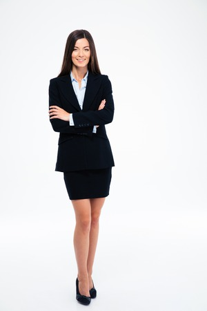arms crossed: Full length portrait of a smiling businesswoman standing with arms folded isolated on a white background. Looking at camera