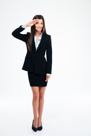 Full length portrait of a cute businesswoman saluting isolated on a white background