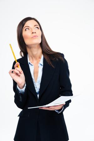 mujer alegre: Empresaria pensativa que sostiene un lápiz con el cuaderno y mirando hacia arriba aislados sobre un fondo blanco