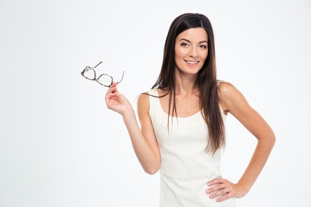 eyeglasses: Smiling woman holding glasses and looking at camera isolated on a white background