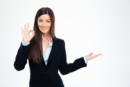 Happy businesswoman showing ok sign and holding copyspace on the palm isolated on a white background. Looking at camera