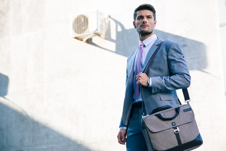 Portrait of a confident businessman standing outdoors near office building