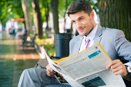 daily newspaper: Smiling businessman sitting on the bench with newspaper and looking at away in park