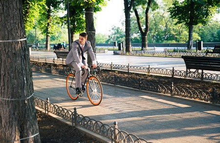 work: Handsome businessman riding bicycle to work in park