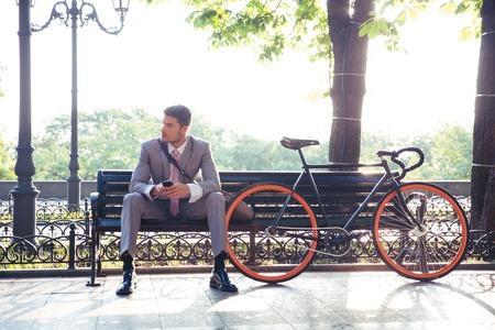 banc de parc: Réfléchi affaires assis sur le banc smartphone extérieur. En regardant au loin Banque d'images