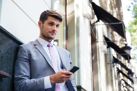 handsome young man: Portrait of a pensive businessman holding smartphone outdoors and looking away