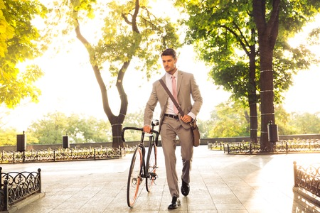 serious businessman: Confident young businessman walking with bicycle on the street in town Stock Photo