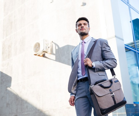 serious businessman: Portrait of a handsome businessman standing outdoors near office building Stock Photo