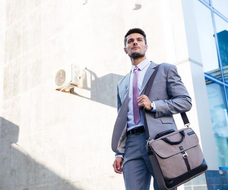 Portret van een knappe zakenman die zich buiten de buurt van het kantoorgebouw