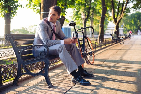 associates: Young businessman sitting on the bench in city park and looking away Stock Photo