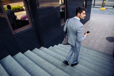 pasear: Hombre de negocios con tel�fono inteligente caminando en las escaleras al aire libre y que mira lejos