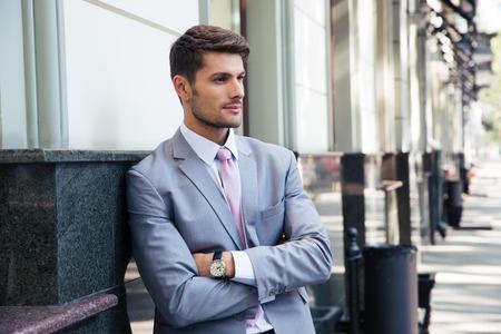 personas mirando: Retrato de un hombre de negocios pensativo con los brazos cruzados de pie al aire libre en la ciudad Foto de archivo