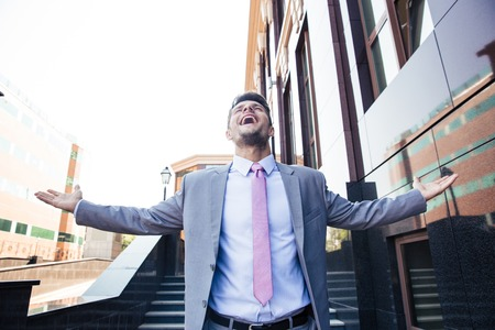 Handsome excited businessman celebrating his success outdoors