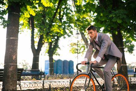 bicicleta: Empresario montar en bicicleta a trabajar en el parque en la ma�ana