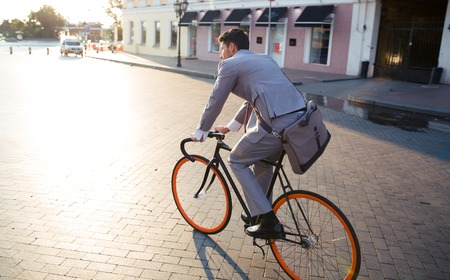 environmental: Businessman riding bicycle to work on urban street in morning