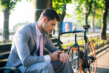 human wrist: Young businessman sitting on the bench outdoors and looking on wrist watch
