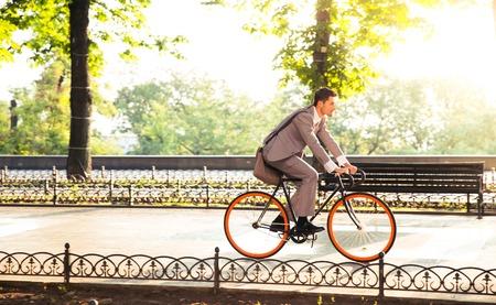 andando en bicicleta: Apuesto hombre de negocios que monta la bicicleta a trabajar en el parque Foto de archivo