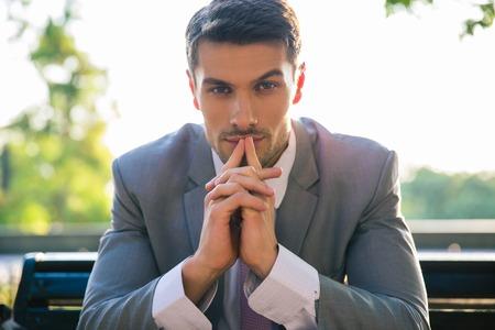 Portret van een zakenman zittend op de bank in openlucht en het denken