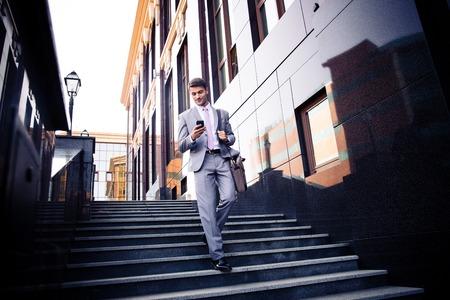 traje: Hombre de negocios feliz caminando en las escaleras y usa smartphone al aire libre Foto de archivo
