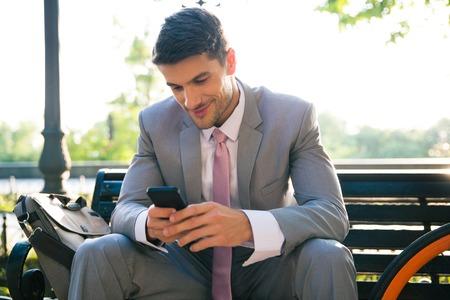행복 한 사업가 야외 벤치에 앉아 스마트 폰을 사용하여