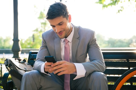 Happy businessman sitting on the bench outdoors and using smartphone