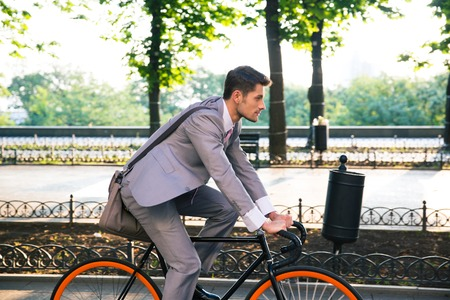 cities: Businessman riding bicycle to work in city park