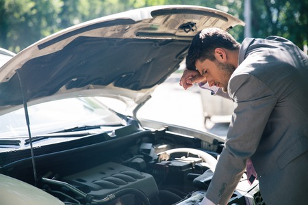 Young man looking under the hood of breakdown car
