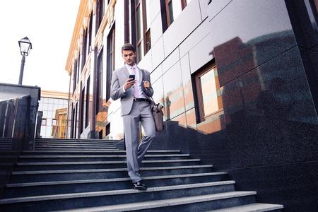 ビジネスマンの階段と屋外のスマート フォンを使用して