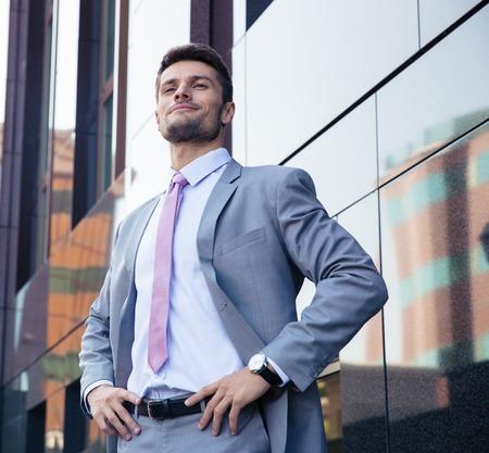 Portrait eines glücklichen zuversichtlich Geschäftsmann in Anzug stehend im Freien Standard-Bild