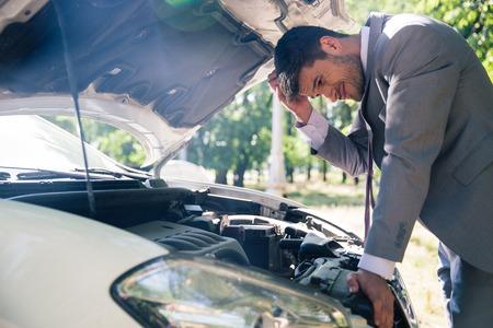 under a tree: Man in suit looking under the hood of breakdown car outdoors