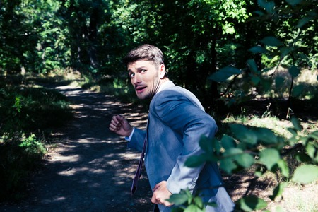 Frightened businessman running away from something outdoors in park Stockfoto
