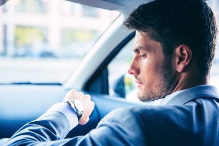 Knappe zakenman die op horloge in de auto